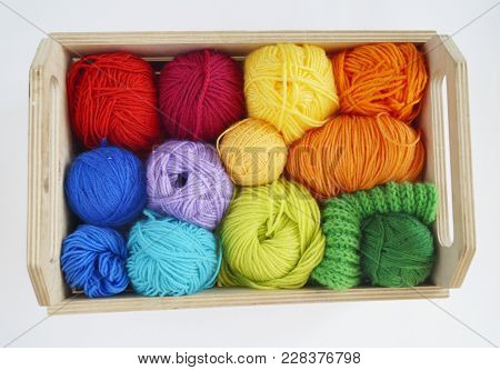 Colorful woolen balls of yarn. Balls of yarn are in the basket. Needlework. Knitting. Threads of red