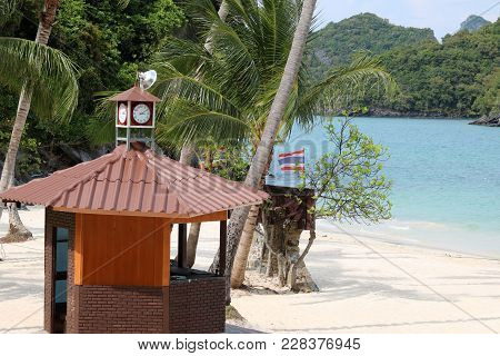 Clock On The Roof Of Lifeguard Tower On The Beach With Ocean Views Background
