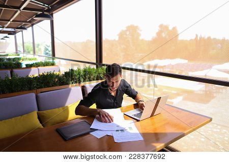 Copywriter Typing Article From Papers On Laptop Keyboard And Hurrying. Hardworking Dressed In Black