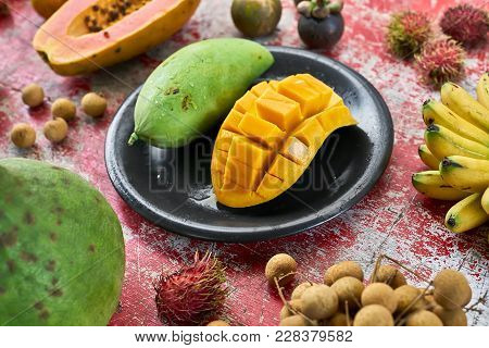 Fresh Exotic Fruit On The Shabby Wooden Red Table. There Are Mangoes On The Black Plate, Bananas, Ly