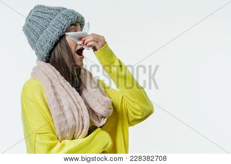 Woman In A Sweater, Knitted Hat, Scarf Sneezes With A Handkerchief. Season Of The Common Cold, Virus