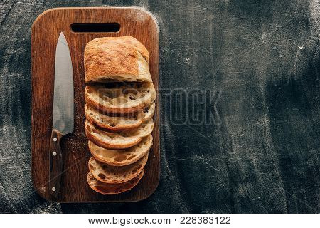 Top View Of Arranged Pieces Of Ciabatta On Cutting Board With Knife On Dark Surface With Flour