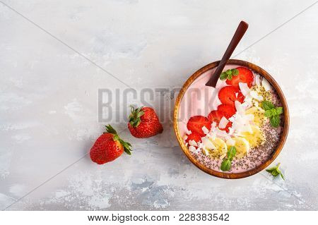 Strawberry Pink Smoothies Bowl With Banana, Coconut And Chia Seeds. Healthy Vegan Food Concept.