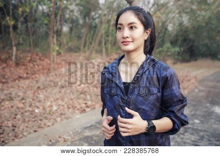 Asian Women Running And Jogging During Outdoor On Road In Park