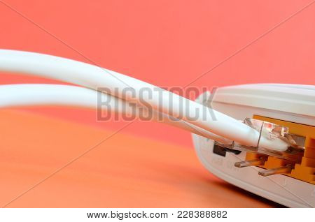 The Internet Cable Plugs Are Connected To The Internet Router, Which Lies On A Bright Orange Backgro
