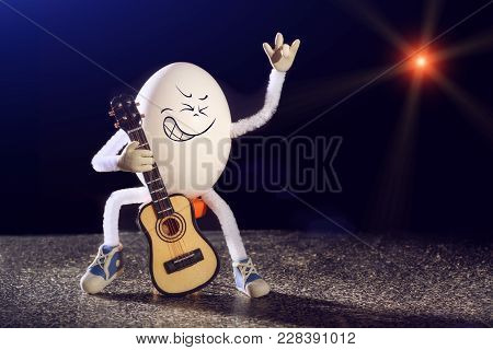 Funny Egg Rocker Guitarist Sitting On A Chair With Guitar On A Stage.