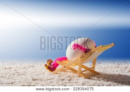 Happy Egg Lying In A Chaise Longue On A Sandy Beach And Enjoy The Sea. Vacation And Travel Concept.