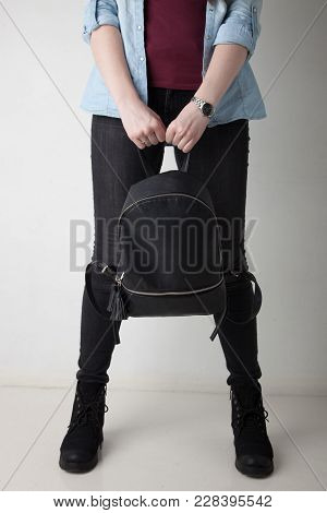 Women's Legs In The City Street. Blue Cropped Denim Jeans, Black High Heel Sandals And Black Backpac