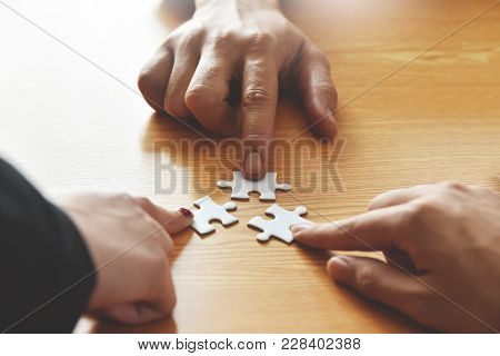 Group Of Business People Hands Are Holding Jigsaw Puzzle On Desk And Solving Puzzle Together At Meet