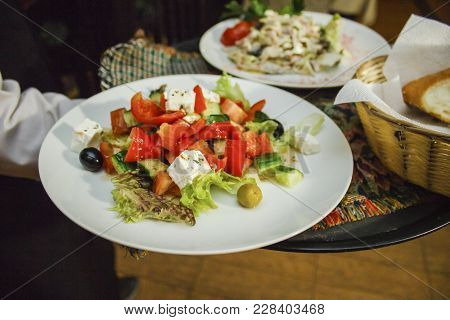 Greek Salad With Tomatoes, Cheese, Peking Cabbage And Olives Is Ready To Serve On The Dining Table.