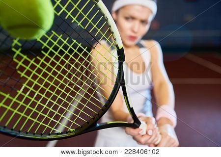 Portrait Of Forceful Woman Playing Tennis In Indoor Court, Focus On Tennis Racket Hitting Ball, Copy