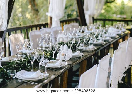 Decorated Elegant Wooden Table For A Wedding Feast In The Gazebo In The Rustic Style With Eucalyptus