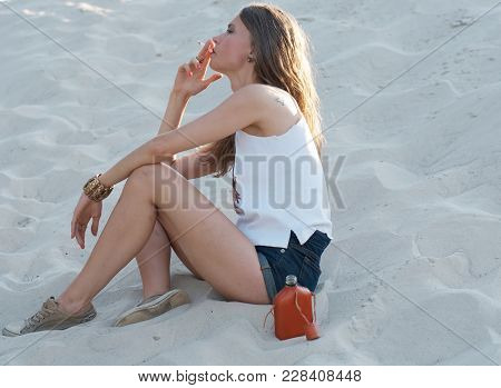 Young Beautiful Woman Sits On The Sand And Smokes A Cigarette