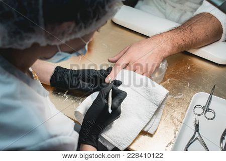 Close-up Of A Manicurist Cleaning Off The Cuticle From The Person's Fingers