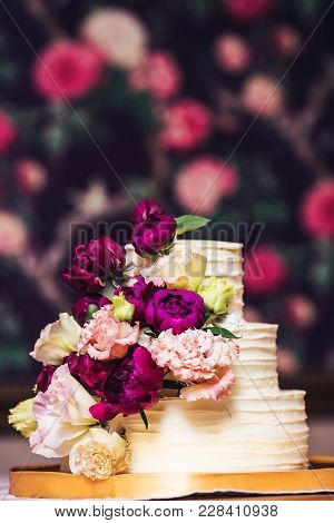 Three-tiered Wedding Cake Decorated With Beautiful Flowers.