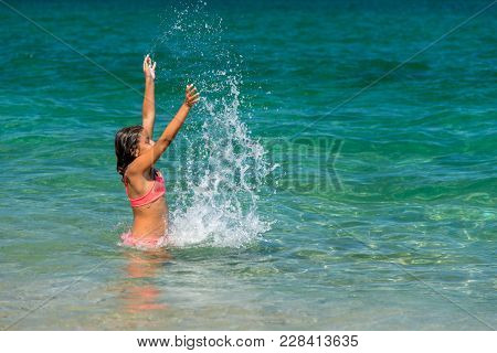 Girl Having Fun Bathing In To The Sea And Splashing Water
