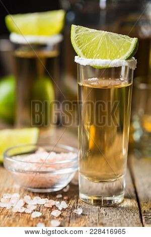 Mexican Gold Tequila Shots With Lime And Salt On Wooden Table Over Black Background