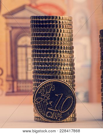 Coin Of Ten Euro Cents On The Background Of Folded Coins And A Paper Bill Of Fifty Euros. Euro Money