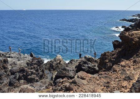 Rocks Near Sea In Tenerife With  A Lot Of Fisherman On Hillside