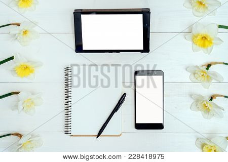 Top View On Table With Narcissus, Empty Diary, Pencil, Tablet And Phone, Free Space. Yellow Narcissu