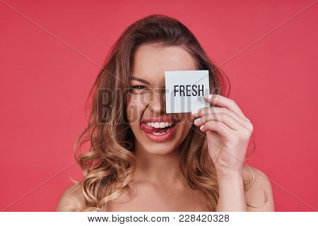 Fresh!  Playful Young Woman Sticking Out Tongue And Smiling While Standing Against Pink Background