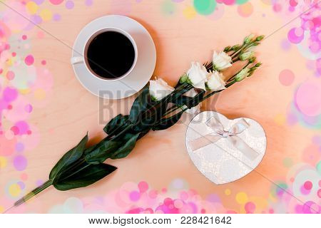 White Cup Of Coffee, Heart Shape Gift Box  And White Eustoma Flower. Top View
