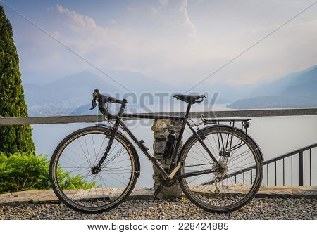 Touring Bicycle Next To Railing With The Beautiful View Of Lake Como, Lombardy, Italy Towards Bellag