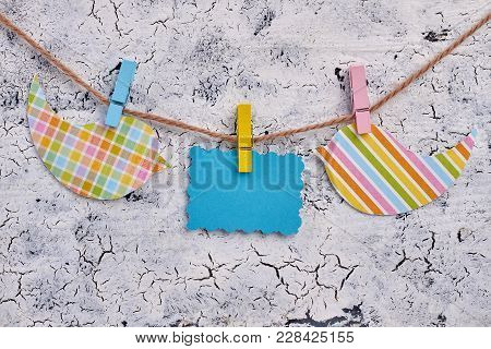 Blank Card Hanging On Clothesline. Blue Empty Note And Patterned Paper Cutout Birds Hanging On Rope,