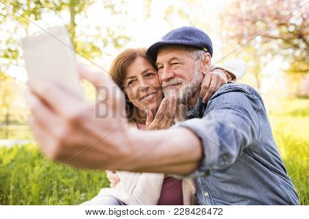 Beautiful Senior Couple In Love On A Walk Outside In Spring Nature Under Blossoming Trees. Man And W