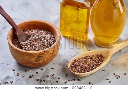 Brown Flax Seeds In Wooden Plate And Flaxseed Oil In Glass Bottle On Brown Rustic Wooden Background,