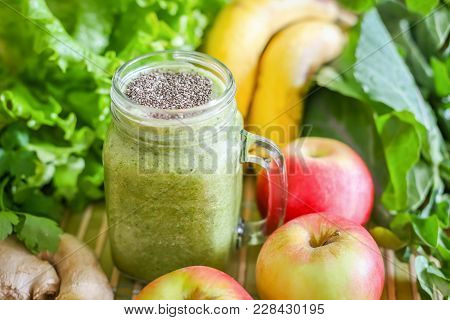 A Glass Of Green Smoothie Surrounded By Fresh Fruit And Green Leafy Vegetables.