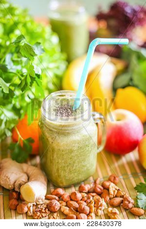 A Glass Of Green Smoothie With A Straw Surrounded By Fresh Fruit And Green Leafy Vegetables.
