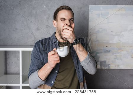 Exhausted Yawning Young Man With Cup Of Coffee