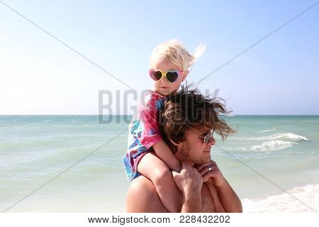 Little Toddler Girl Sitting On Father's Shoulders On Beach By The Ocean