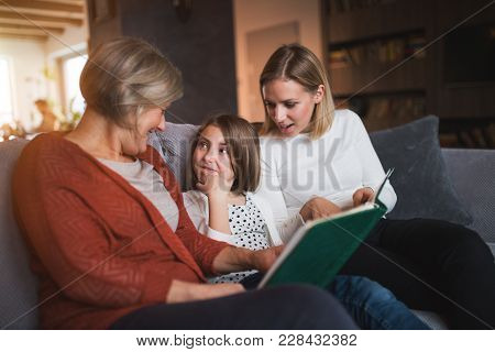 A Small Girl With Her Mother And Grandmother At Home. Family And Generations Concept.