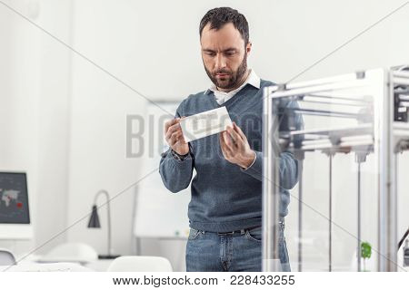 Careful Inspection. Pleasant Young Man Standing In The Office And Looking At The Model Printed On A