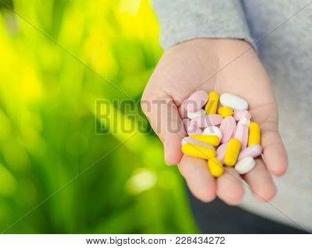 Close-up Woman Hand Holding A Lot Of Different Pills. Health Care And Medical Concept.