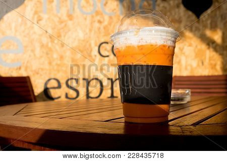 Iced Milk Tea Or Iced Thai Tea On Wooden Table