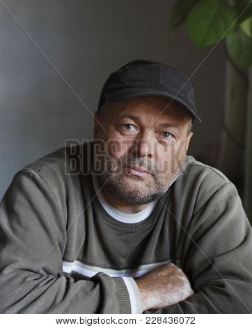 Middle-aged Man Of Strong Build With Bristle On Face In A Black Cap And A Gray-green Jumper,looks St