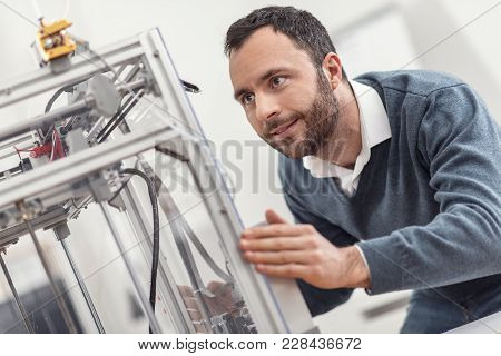 Careful Treatment. Charming Bearded Young Man Touching The Body Of A 3d Printer And Trying To Move I
