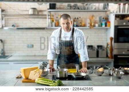 Handsome Male Chef In The Kitchen Interior. The Cook Is Getting Ready To Cook A Dish