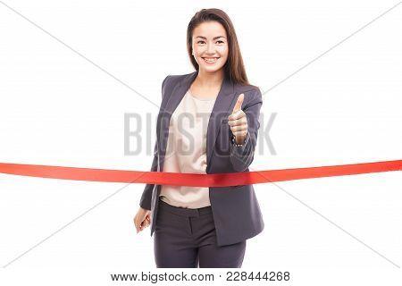 Portrait Of Happy Asian Businesswoman Posing Near Red Ribbon On Finish Line