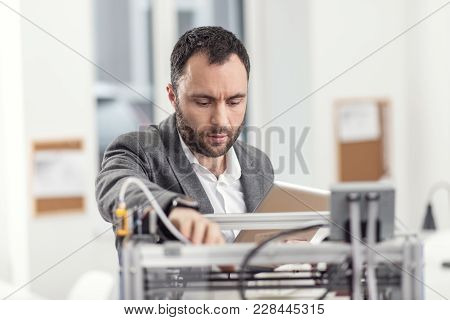 Experienced Troubleshooter. Pleasant Bristled Young Engineer Using A Tablet And Trying To Fix Proble