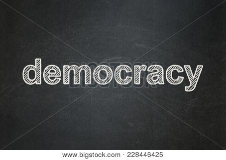 Politics Concept: Text Democracy On Black Chalkboard Background