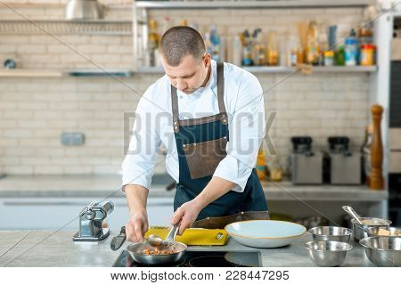 Chef Holding Frying Pan. Chef Is Stirring Dish In Frying Pan At Professional Kitchen Interior. Prepa