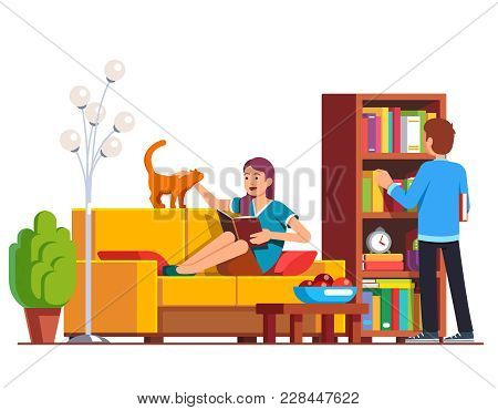 Husband And Wife Relaxing And Reading At Home Living Room. Man Picking Book From Wooden Bookcase, Wo