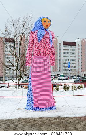 Gomel, Belarus - February 18, 2018: Scarecrow Of Shrovetide Against Backdrop Of City Buildings At Ce