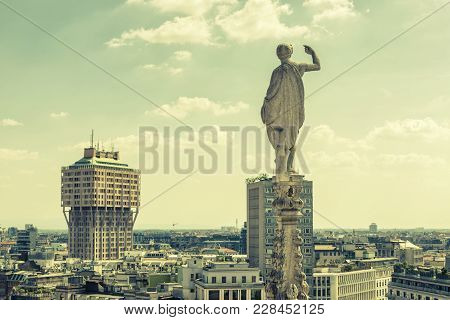 Milan Skyline, Italy. Marble Statue On The Spire Of Milan Cathedral Overlooking Milan. Scenic Panora
