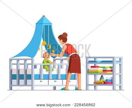 Mother Playing Rattle To Little Baby Son Toddler Sitting In Crib Bed Or Cot. Woman Babysitter Lookin