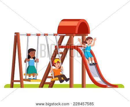 Happy Boy Swinging On Swing, Girl Sliding Down Slide In Public Park Or Kindergarten Playground. Pres